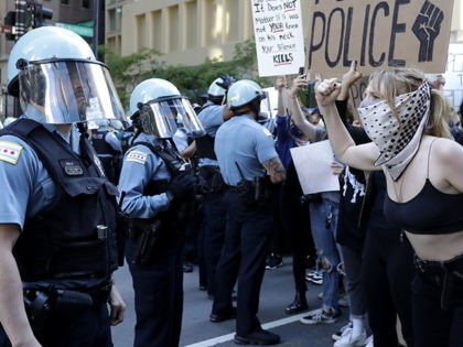 People confront police officers during a protest over the death of George Floyd in Chicago, Saturday, May 30, 2020. Protests were held throughout the country over the death of George Floyd, a black man who died after being restrained by Minneapolis police officers on May 25. (AP Photo/Nam Y. Huh)