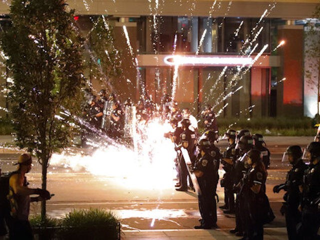 A firework explodes by a police line as demonstrators gather to protest the death of George Floyd, Saturday, May 30, 2020, near the White House in Washington. Floyd died after being restrained by Minneapolis police officers. (AP Photo/Alex Brandon)
