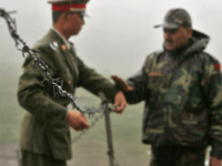 In this July 5, 2006 file photo, a Chinese soldier, left, and an Indian soldier put into place a barbed wire fence removed temporarily for Chinese officials to cross back to their country after a meeting with their Indian counterparts at the international border at Nathula Pass, in northeastern Indian …