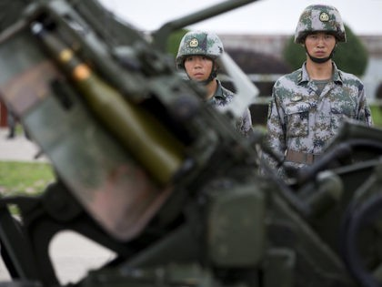 Soldiers stand near the PG59 57mm anti-aircraft artillery gun after conducting a demonstration at a base of People's Liberation Army Lanzhou Military 47th Combined Corps anti-air brigade in Xi'an in northwest China's Shaanxi province Monday, July 29, 2013. (AP Photo/Andy Wong)