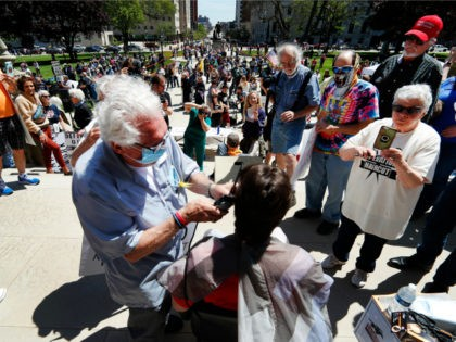 Barber Karl Manke, of Owosso, gives a free haircut on the steps of the State Capitol during a rally in Lansing, Mich., Wednesday, May 20, 2020. Barbers and hair stylists are protesting the state's stay-at-home orders, a defiant demonstration that reflects how salons have become a symbol for small businesses …
