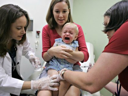 Duncan Barnes, 1, is held by his mother, Jennifer Barnes, while receiving a vaccine for swine flu from Dr. Susan Henderson, left, and a vaccine for seasonal flu from nurse Allison Ross at Emory Children's Center in Atlanta in 2009. (Photo: File photo by John Amis, AP)
