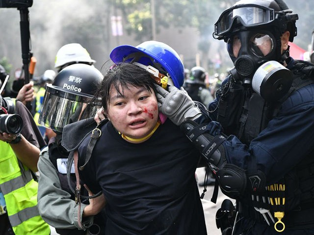 TOPSHOT - Protesters are detained by police near the Hong Kong Polytechnic University in Hung Hom district of Hong Kong on November 18, 2019. - Pro-democracy demonstrators holed up in a Hong Kong university campus set the main entrance ablaze on November 18 to prevent surrounding police moving in, after …