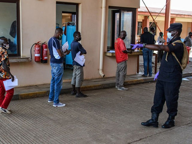An Ugandan security officer asks for social distancing as truck drivers wait in a line to go through the Uganda's immigration office in Malaba, a city bordering with Kenya, in Uganda, on April 29, 2020. - All truck drivers ferrying goods crossing the border from Kenya must take a test …