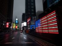 TOPSHOT - The US Flag illuminates a street in Times Square amid the Covid-19 pandemic on April 30, 2020 in New York City. (Photo by Johannes EISELE / AFP) (Photo by JOHANNES EISELE/AFP via Getty Images)