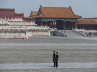 Paramilitary police officers wear face masks as a preventive measure against the COVID-19 coronavirus as they stand guard in the Forbidden City, the former palace of China's emperors, in Beijing on May 1, 2020. - With optimism and a heavy dose of caution, millions of Chinese hit the road or …