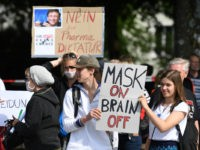 MUNICH, GERMANY - MAY 16: Protesters hold signs reading Mask on, brain off and I am not a conspirator, I am just a mother and Give Gates no chance during a protest of about 1000 people against lockdown measures and other government policies relating to the novel coronavirus crisis on …