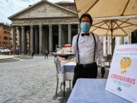 A waiter is pictured at a cafe terrace by the Pantheon monument in central Rome on May 18, 2020 during the country's lockdown aimed at curbing the spread of the COVID-19 infection, caused by the novel coronavirus. - Restaurants and churches reopen in Italy on May 18, 2020 as part …