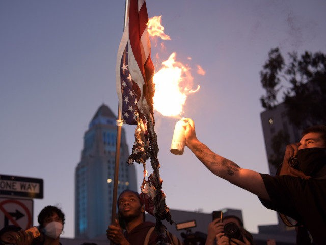 A man burns an upsidedown US flag as protesters gather in downtown Los Angeles on May 27, 2020 to demonstrate after George Floyd, an unarmed black man, died while being arrested by a police officer in Minneapolis who pinned him to the ground with his knee. - Outrage has grown …