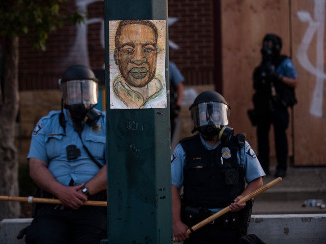 MINNEAPOLIS, MN - MAY 27: A portrait of George Floyd hangs on a street light pole as police officers stand guard at the Third Police Precinct during a face off with a group of protesters on May 27, 2020 in Minneapolis, Minnesota. The station has become the site of an …