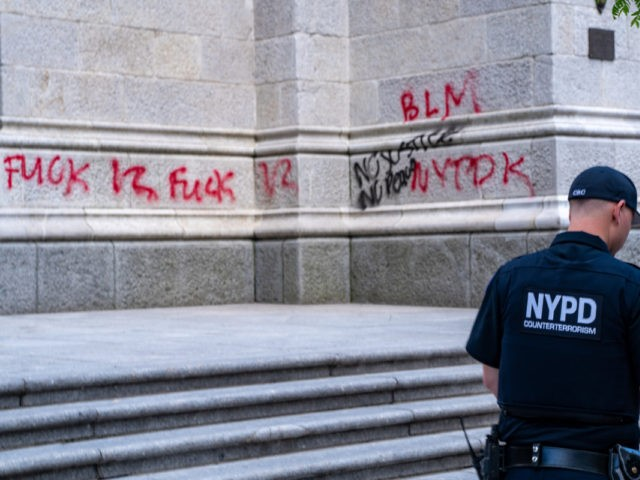 NEW YORK, NEW YORK - MAY 30: An NYPD officer walks by a vandalized St. Patrick's Cathedral on May 30, 2020 in New York City. Minneapolis Police officer Derek Chauvin was filmed kneeling on George Floyd's neck. Floyd was later pronounced dead at a local hospital. Across the country, protests …