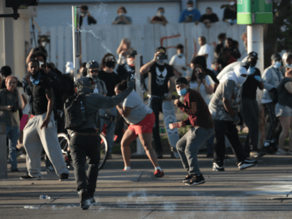 ST. PAUL, MINNESOTA - MAY 28: Protesters throw objects at police on May 28, 2020 in St. Paul, Minnesota. Today marks the third day of ongoing protests after the police killing of George Floyd. Four Minneapolis police officers have been fired after a video taken by a bystander was posted …