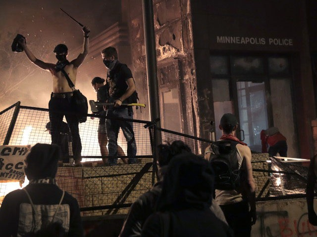 MINNEAPOLIS, MINNESOTA - MAY 28: Protesters gather in front of the 3rd precinct police building while it burns on May 28, 2020 in Minneapolis, Minnesota. Today marks the third day of ongoing protests after the police killing of George Floyd. Four Minneapolis police officers have been fired after a video …