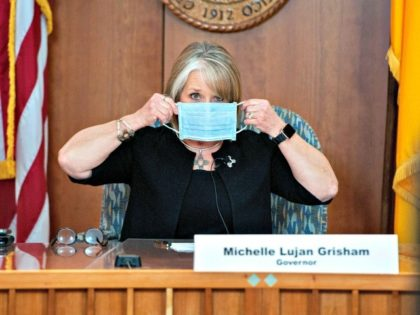 Gov. Michelle Lujan Grisham holding a face mask in between speaking at a coronavirus press conference in Santa Fe, N.M.Credit...Eddie Moore/The Albuquerque Journal, via Associated Press