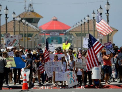 Law enforcement personnel on horseback keep protestors on the sidewalk during a May Day demonstration at the pier Friday, May 1, 2020, in Huntington Beach, Calif. (AP Photo/Chris Carlson)