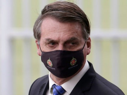 "Brazilian President Jair Bolsonaro wears a mask due to the COVID-19 pandemic as he leaves his official residence, Alvorada palace, in Brasilia, Brazil, Monday, May 18, 2020. The logo on the mask reads ""Military Police. Federal District."" (AP Photo/Eraldo Peres)"