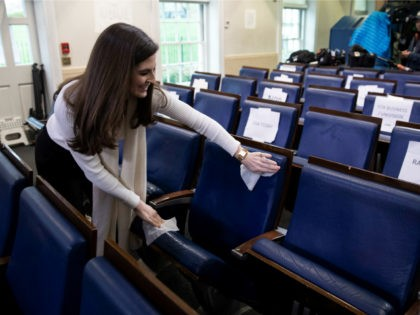 CNN's Kaitlan Collins cleans a seat in the James Brady Briefing Room before President Donald Trump speaks about the coronavirus, Monday, March 23, 2020, in Washington. (AP Photo/Alex Brandon)