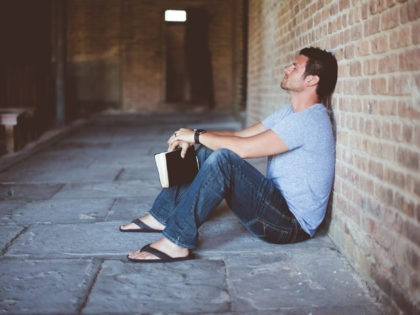 A man sits on the ground outside of a church with his Bible in his hands, apparently praying.