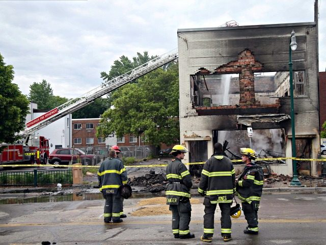 Firefighters stand as an aerial hose sends water on hot spots of a building destroyed near the Minneapolis Police Third Precinct Thursday, May 28, 2020, in Minneapolis, after a night of rioting and looting as protests continue over the death of George Floyd, who was seen on video gasping for …