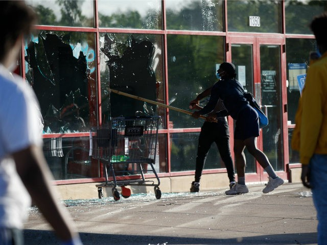 A man breaks a window at a tire store Thursday, May 28, 2020, in St. Paul, Minn. Minnesota Gov. Tim Walz called in the National Guard on Thursday as looting broke out in St. Paul and a wounded Minneapolis braced for more violence after rioting over the death of George …