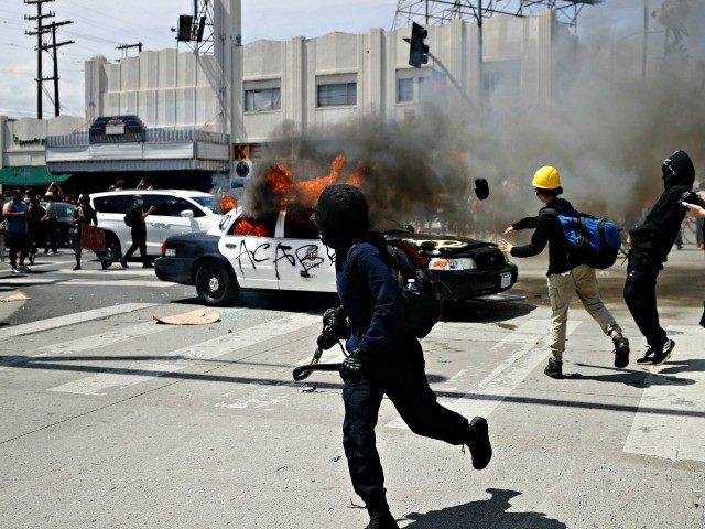 LOS ANGELES, CALIFORNIA - MAY 30: An LAPD vehicle burns after being set alight by protestors during demonstrations following the death of George Floyd on May 30, 2020 in Los Angeles, California. The vast majority of protestors demonstrated peacefully. Former Minneapolis police officer Derek Chauvin was taken into custody for Floyd's death. Chauvin has been accused of kneeling on Floyd's neck as he pleaded with him about not being able to breathe. Floyd was pronounced dead a short while later. Chauvin and 3 other officers, who were involved in the arrest, were fired from the police department after a video of the arrest was circulated. (Photo by Mario Tama/Getty Images)