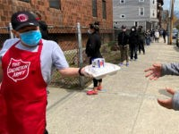 A Salvation Army worker, left, wears a mask out of concern about the coronavirus while handing out a lunch box as people form a line along a sidewalk in front of a Salvation Army food pantry, Tuesday, April 21, 2020, in Chelsea, Mass. (AP Photo/Rodrique Ngowi)