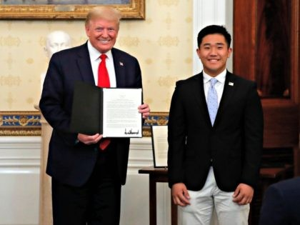 President Donald Trump poses for a photo with TJ Kim, a sophomore at The Landon School, during an event to honor volunteers helping to battle the coronavirus, in the Blue Room of the White House, Friday, May 1, 2020, in Washington. (AP Photo/Alex Brandon)