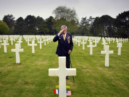 In this May 1, 2019 file photo, World War II and D-Day veteran Charles Norman Shay, from Indian Island, Maine, salutes the grave of fellow soldier Edward Morozewicz at the Normandy American Cemetery in Colleville-sur-Mer, Normandy, France. Instead of parades, remembrances, embraces and one last great hurrah for veteran soldiers …