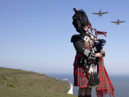 Pipe major Andy Reid of The Scots Guards plays his pipes on the cliffs of Dover, Kent, as two Spitfires from the Battle of Britain memorial flight fly overhead, ahead of commemorations to mark the 75th anniversary of VE Day Friday May 8, 2020. (Richard Pohle/The Times via AP)