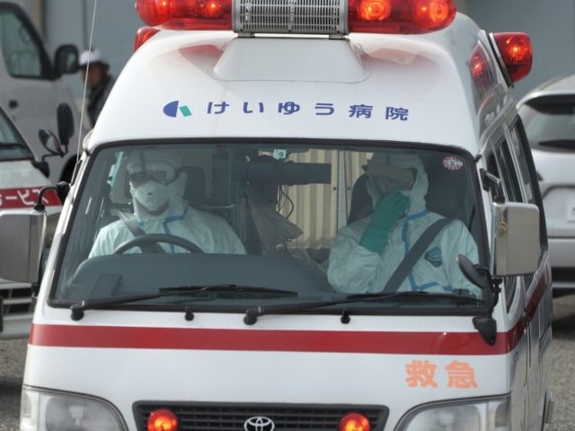 Officials in protective suits drive an ambulance near the cruise ship Diamond Princess anchored at the Yokohama Port in Yokohama, near Tokyo Friday, Feb. 7, 2020. Japan on Friday reported 41 new cases of a virus on a cruise ship that's been quarantined in Yokohama harbor while the death toll …