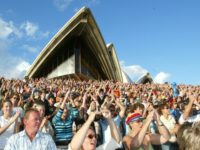 "A crowd of more than 4,000 Australians at the Opera House in Sydney wave to TV cameras as the live telecast Australia Unites, ""Reach out to Asia"" concert goes to air Saturday, Jan. 8, 2005. The live to air concert is a fundraising effort for victims of the south-Asian earthquake …"