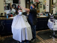 Eli Resendez, left, owner of the Barber Shop 32 in Westfield, Ind. and his brother Chuy Resendez, cut hair of customers Will Gount, left, and Chad Reeh as the shop opened on Monday, May 11, 2020. Barber shops have been closed to prevent the spread of the coronavirus since March …