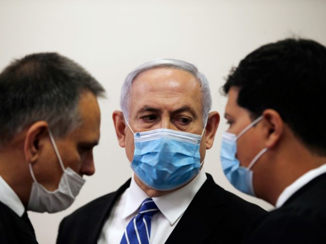 Israeli Prime Minister Benjamin Netanyahu, wearing a face mask in line with public health restrictions due to the coronavirus pandemic, looks at his lawyer inside the court room as his corruption trial opens at the Jerusalem District Court, Sunday, May 24, 2020. He is the country's first sitting prime minister …