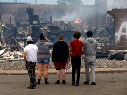 Onlookers watch as smoke smolders from a destroyed fast food restaurant near the Minneapolis Police Third Precinct, Thursday, May 28, 2020, after a night of rioting and looting as protests continue over the death of George Floyd, who died in police custody Monday night in Minneapolis after video shared online …