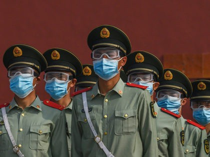 BEIJING, CHINA - MAY 02: Chinese paramilitary police wear protective masks as they guard the entrance to the Forbidden City as it re-opened to limited visitors for the May holiday, on May 2, 2020 in Beijing, China. Beijing lowered its risk level after more than three months Thursday in advance …