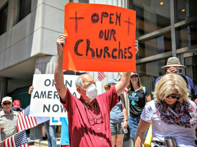Demonstrators holding signs demanding their church to reopen protest during a rally to reopen California and against stay-at-home directives on May 1, 2020, in San Diego, Calif.Sandy Huffaker / AFP - Getty Images