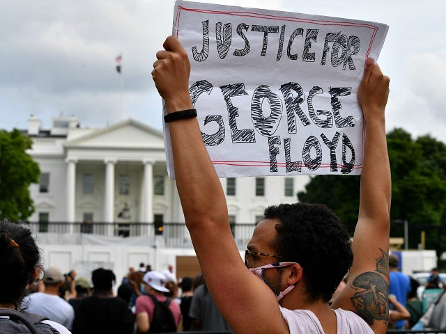 Protesters hold signs as they gather outside the White House in Washington, DC, on May 29, 2020 in a demonstration over the death of George Floyd, a black man who died after a white policeman kneeled on his neck for several minutes. - Demonstrations are being held across the US …