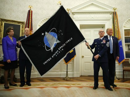 President Donald Trump stands as Chief of Space Operations at US Space Force Gen. John Raymond, second from left, and Chief Master Sgt. Roger Towberman, second from right, hold the United States Space Force flag as it is presented in the Oval Office of the White House, Friday, May 15, …