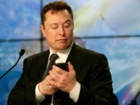 Elon Musk founder, CEO, and chief engineer/designer of SpaceX jokes with reporters as he pretends to be searching for an answer to a question on a cell phone during a news conference after a Falcon 9 SpaceX rocket test flight to demonstrate the capsule's emergency escape system at the Kennedy …