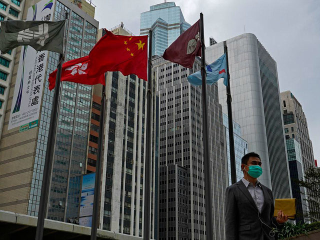 A man wears protective face masks walk past a Chinese national flag on a street in Hong Kong, Monday, Feb, 3, 2020. In Hong Kong, thousands of health care workers were threatening to go on strike Tuesday unless the government agrees to talks before a 6 p.m. Monday deadline. Hong …
