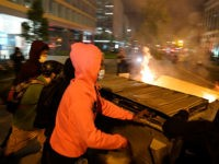 Demonstrators push a dumpster that is on fire towards a police line as people protest the death of George Floyd, Saturday, May 30, 2020, near the White House in Washington. Floyd died after being restrained by Minneapolis police officers. (AP Photo/Evan Vucci)