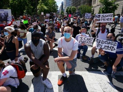 People protesting the death of George Floyd kneel to pray at Lafayette Square next to the White House on May 31, 2020 in Washington,DC. - Thousands of National Guard troops patrolled major US cities after five consecutive nights of protests over racism and police brutality that boiled over into arson …