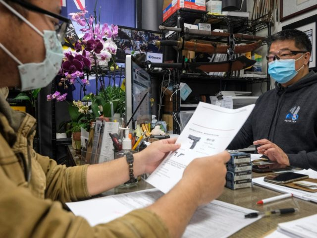 David Liu, right, owner of a gun store, takes an order from a customer in Arcadia, Calif., Sunday, March 15, 2020. Coronavirus concerns have led to consumer panic buying of grocery staples and now gun stores are seeing a run on weapons and ammunition as panic intensifies. (AP Photo/Ringo H.W. …