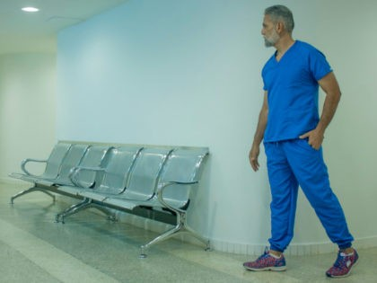 A healthcare worker looks into an empty waiting room.
