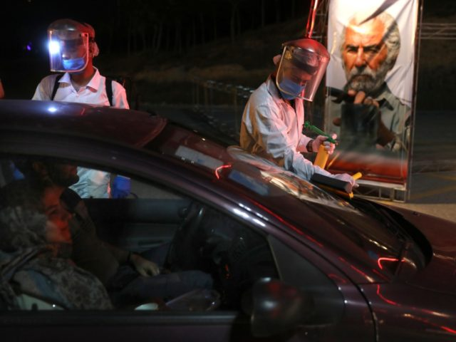 Men wearing protective suits disinfect cars against coronavirus while people enter a new drive-in cinema for watching a movie on a car parking area of the Milad telecommunications tower, as regular theaters are closed due to the coronavirus outbreak, Friday, May 1, 2020. Iran is the region's epicenter of the …