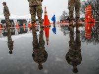 "National Guard personnel stand at attention as they wait for patients to arrive for COVID-19 coronavirus testing facility at Glen Island Park, Friday, March 13, 2020, in New Rochelle, N.Y. State officials have set up a ""containment area"" in the New York City suburb, where schools and houses of worship …"