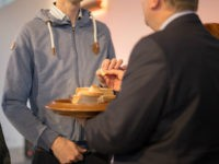 Minister administers communion to man.