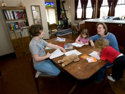 ** TO GO WITH CRISIS ENSENANZA DOMESTICA ** Andrea Farrier sits at her kitchen table with her children Rachel, 8, left, Rebecca, 4, center, and Sarah, 2, right, as they do schoolwork in their home, Friday, Feb. 20, 2009, in Kalona, Iowa. Farrier does double-duty _ homeschooling her daughters and …