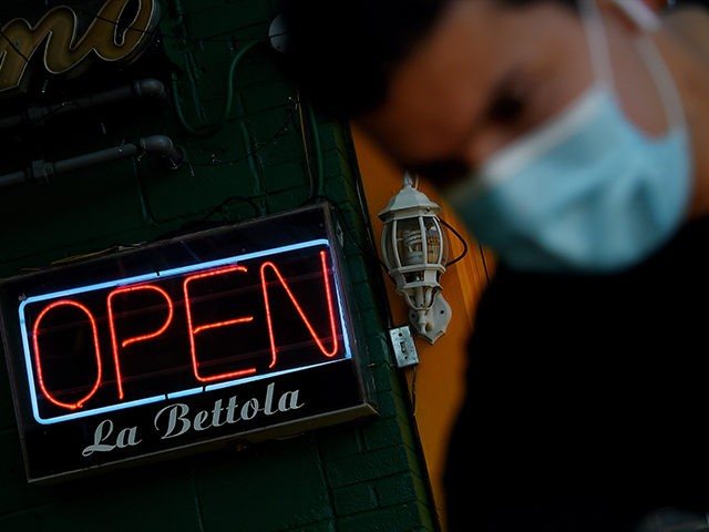 An employee cleans the entrance of a restaurant in the Crystal City neighborhood of Arlington, Virginia, as restaurants and businesses try to adapt to the ever-changing situation amid the coronavirus pandemic, on May 13, 2020. (Photo by Olivier DOULIERY / AFP) (Photo by OLIVIER DOULIERY/AFP via Getty Images)