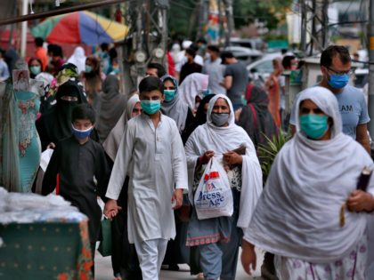 People wearing protective masks visit a market after the government relaxed the weeks-long lockdown that was enforced to curb the spread of the coronavirus, in Rawalpindi, Pakistan, Tuesday, May 12, 2020. (AP Photo/Anjum Naveed)